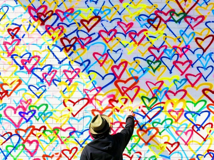 Artista grafita parede com spray, durante visita da primeira-dama dos Estados Unidos, Michelle Obama, no Union Market, em evento de comemoração ao Dia Internacional da Mulher, nesta terça-feira (08)