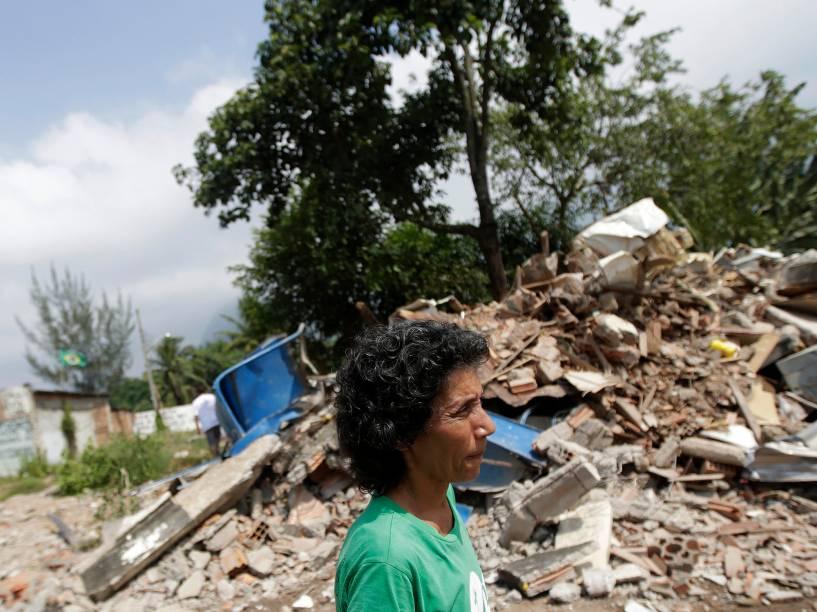 Uma mulher passa em frente aos escombros de uma casa demolida na comunidade Vila Autódromo, no Rio de Janeiro, cercado por obras do Parque Olímpico do Rio, onde algumas famílias ainda lutam contra o despejo