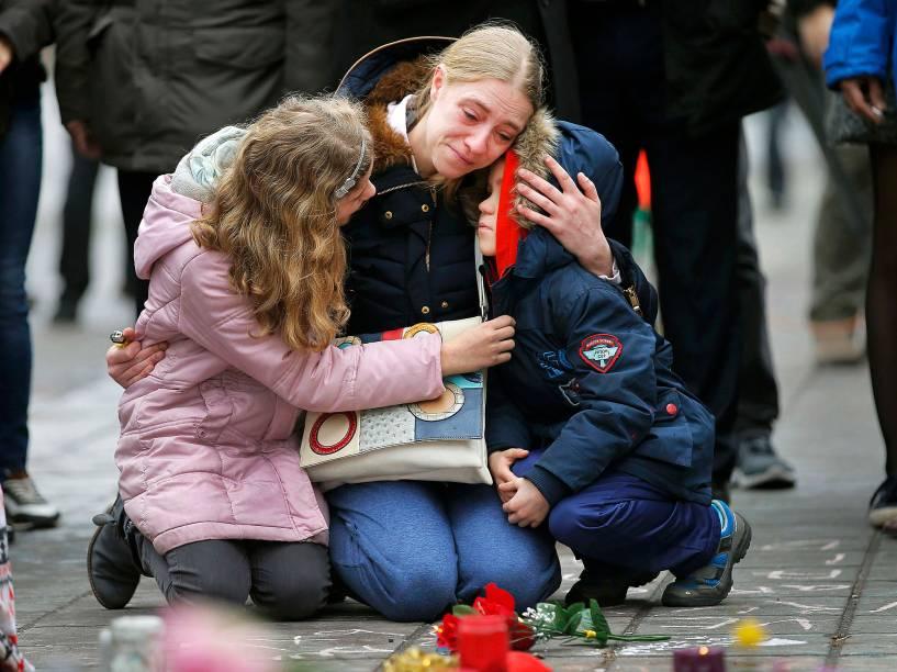 Mulher chora e abraça seus filhos em um memorial às vítimas dos ataques em Bruxelas, na Bélgica