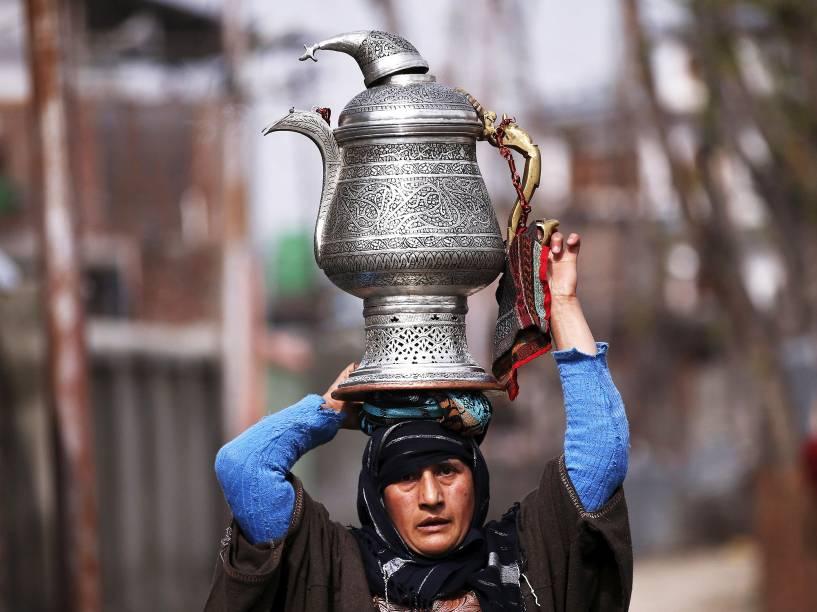 Uma mulher da Caxemira transporta um bule tradicional chamado de samovar na cabeça em uma estrada em Srinagar, nesta quarta-feira (23)
