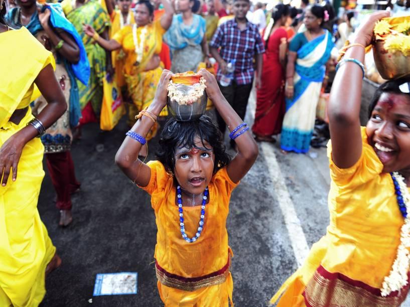 Garota hindu carrega recipiente com leite, em um festival em homenagem a Murugan, divindade hindu. A festa acontece em Chennai, na Índia, onde devotos levam oferendas para afastar os maus-espíritos