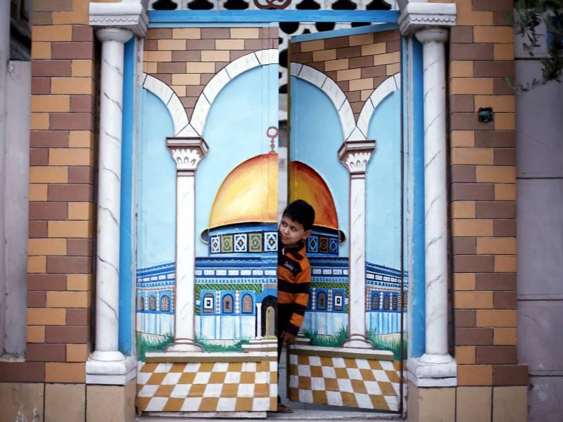 Menino olha da porta de sua casa uma manifestação de militantes do Hamas para marcar o décimo segundo aniversário da morte do xeque Ahmed Yassin, antigo líder do grupo fundamentalista palestino, na Cidade de Gaza - 23/03/2016
