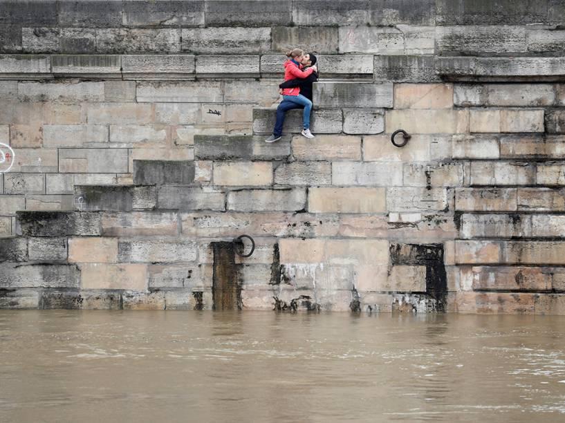 Casal troca beijos sentados em degraus acima do rio Sena, que ultrapassa os níveis normais de água graças às fortes chuvas que o atingiram - 01/06/2016