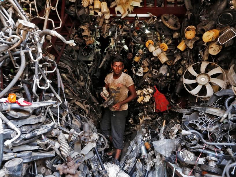 Homem carrega peças de automóveis em loja de autopeças, em Mumbai, na Índia - 01/06/2016