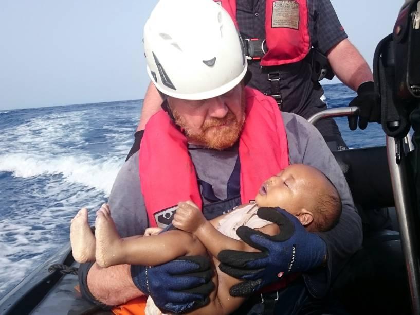 Imagem divulgada em 30 de maio, mostra um socorrista alemão da organização humanitária Sea-Watch com o corpo de um bebê imigrante afogado, resgatado após naufrágio na costa da Líbia - 27/05/2016