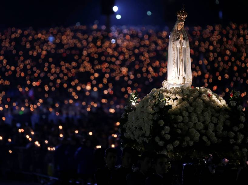 Imagem de Nossa Senhora de Fátima é conduzida por fiéis católicos durante vigília à luz de velas, no 99º aniversário da aparição da Virgem Maria aos três pastorinhos, no santuário de Fátima, em Portugal