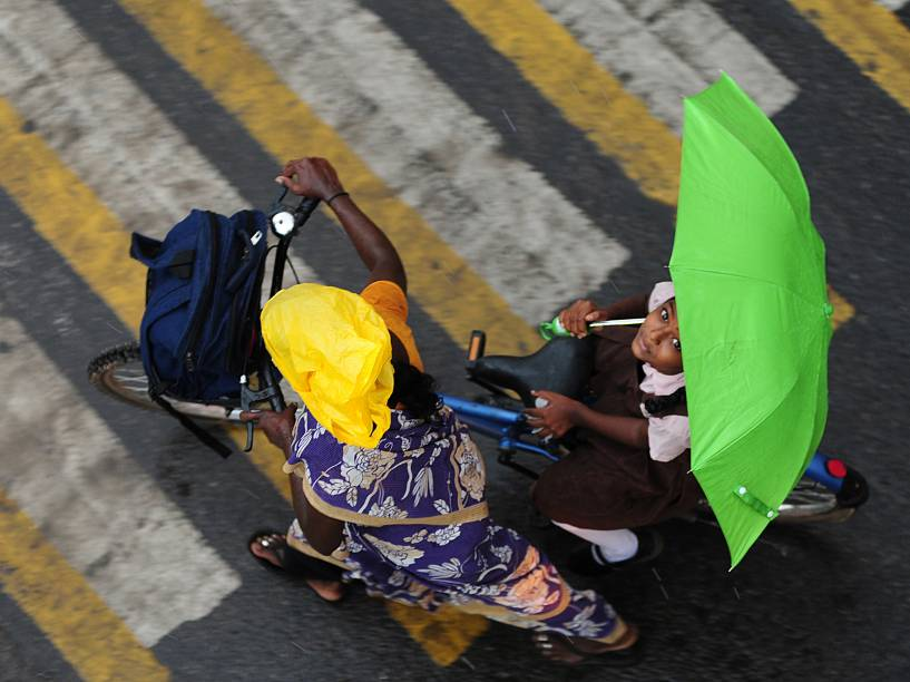 Menina segura um guarda-chuva enquanto atravessar uma estrada na carona de uma bicicleta durante a chuva em Chennai, na Índia - 08/06/2016