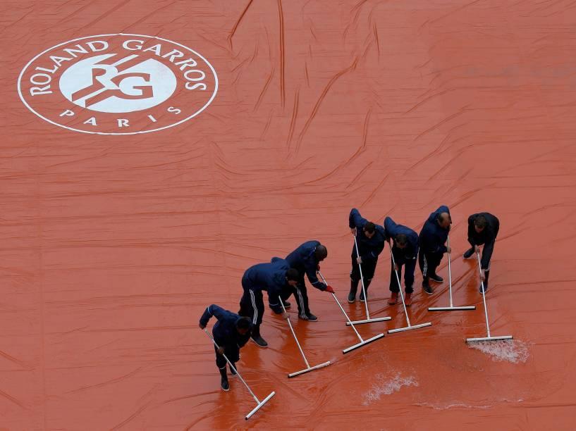 Equipe trabalha para retirar a água da chuva sobre a quadra antes do início da rodada do aberto de tênis da França, em Roland Garros - 31/05/2016