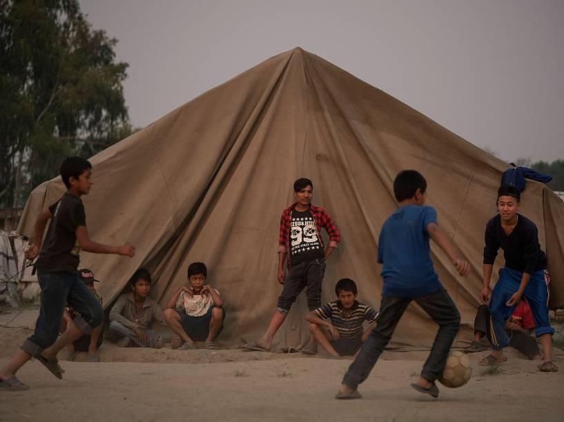 Crianças jogam bola em acampamento improvisado há um ano, para abrigar as vítimas do terremoto em Kathmandu, no Nepal, registrado com o maior que atingiu o país, deixando milhares de mortos - 25/04/2016