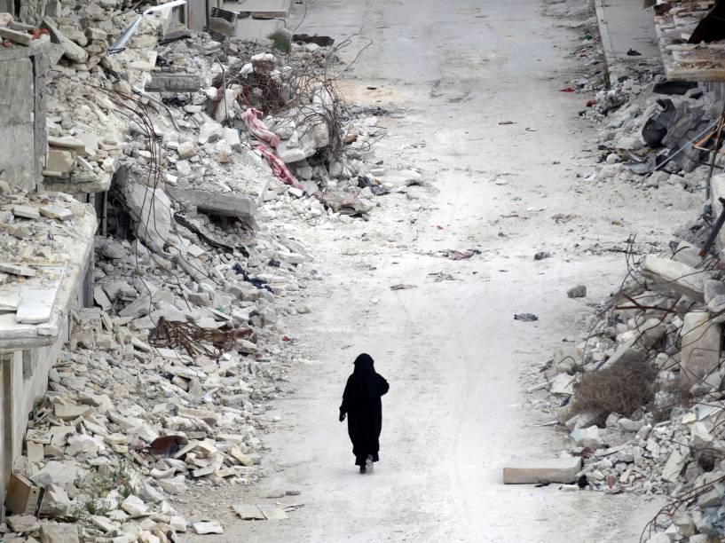 Mulher síria caminha por entre escombros em uma área controlada por rebeldes, na província de Idlib, na Síria - 13/05/2016