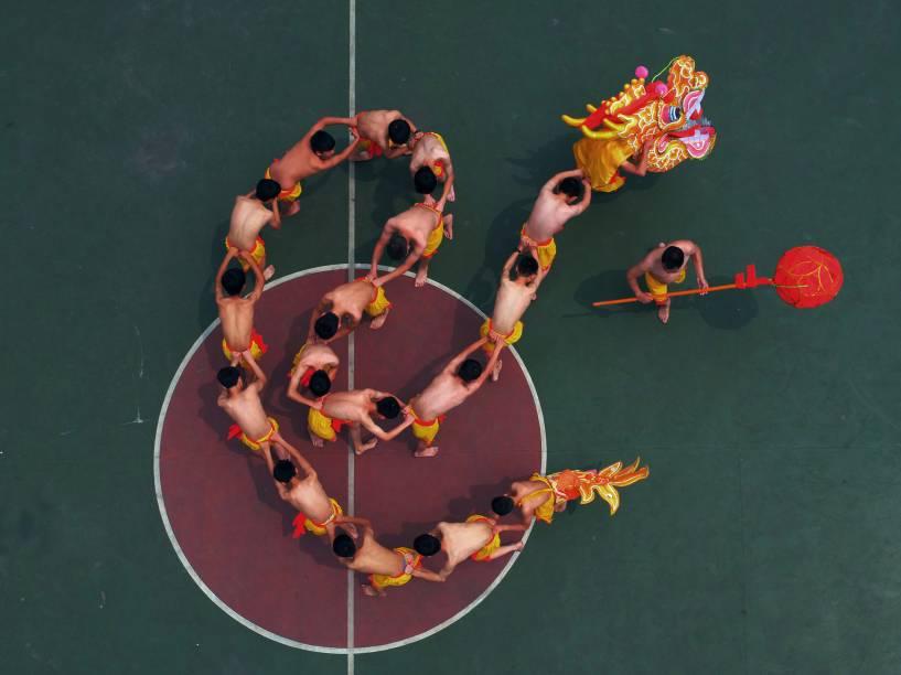 Alunos aprendem a executar uma dança do dragão sob a instrução de um artista local em um parque da cidade de Chongqing, na China