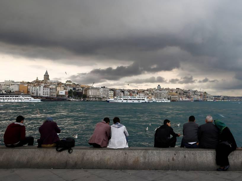 Pessoas observam a paisagem sentados nas margens do Estreito de Bósforo, em Istambul, Turquia - 05/05/2016