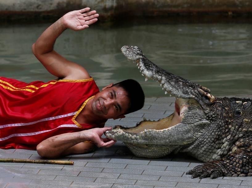 Homem sorri enquanto coloca a cabeça entre as mandíbulas de um crocodilo durante uma performance para os turistas na Sriracha Tiger Zoo, na província de Chonburi, na Tailândia - 07/06/2016