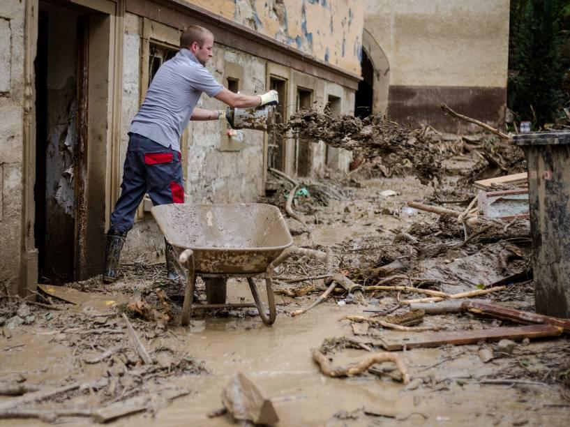 Homem joga lama para fora de sua casa depois de fortes tempestades que deixaram pelo menos quatro pessoas mortas, no sul da Alemanha - 31/05/2016