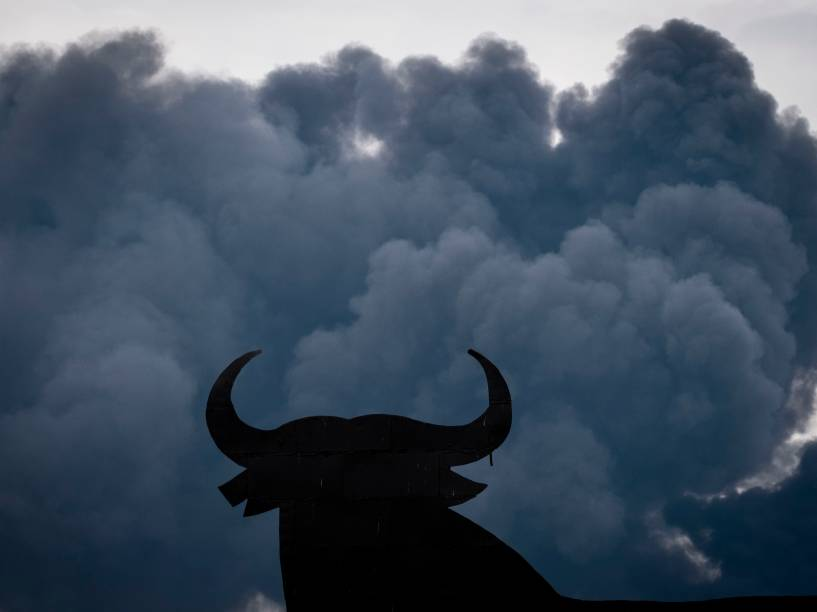 Silhueta de um outdoor em forma de touro é vista entre as nuvens negras de fumaça produzidas pela queima de pneus em um lixão nos arredores de uma zona residencial na cidade de Seseña, na Espanha - 13/05/2016