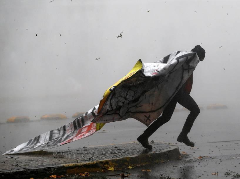 Manifestante foge de nuvem formada por bomba de gás lacrimogêneo, em protesto a favor de melhorias no sistema educacional, em Santiago, Chile - 05/05/2016