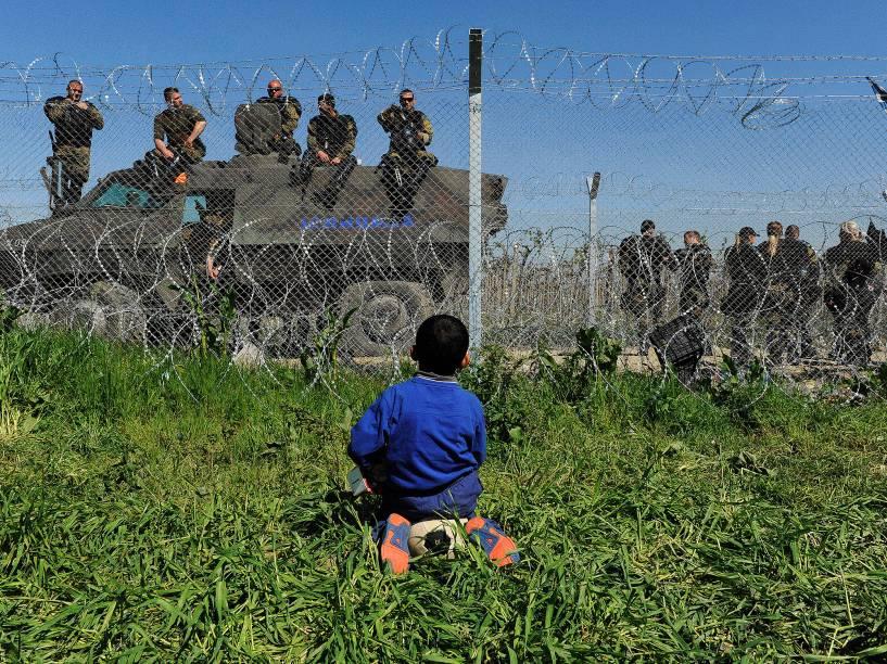 Criança sentada sobre uma bola observa policiais macedônios na fronteira em um acampamento improvisado perto da aldeia de Idomeni, na Grécia - 12/04/2016<br><br><br>