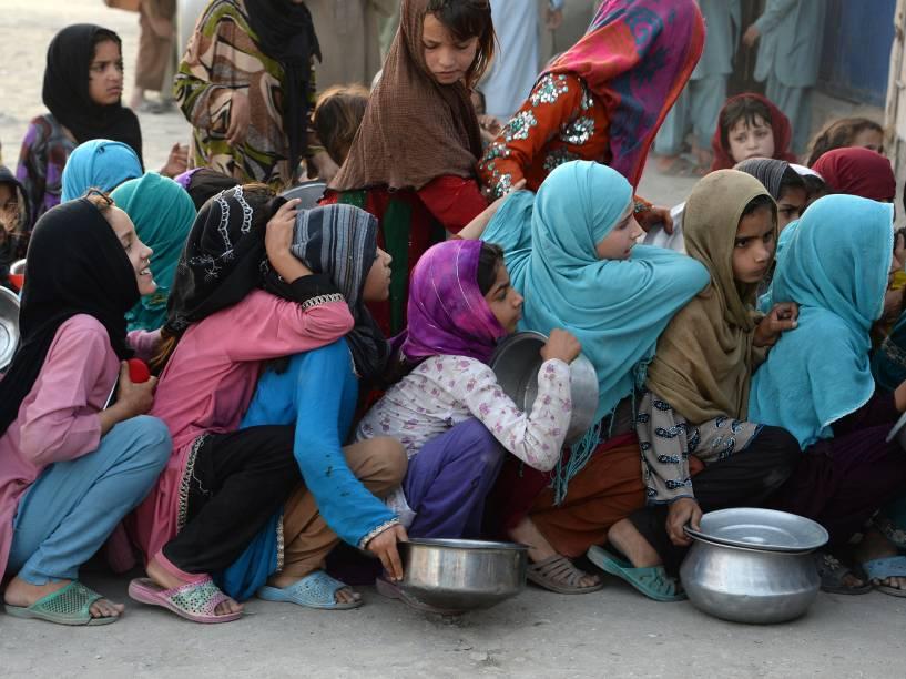 Garotas afegãs seguram recipientes e aguardam em fila para receberem comida de uma instituição privada de caridade, durante o período do Ramadan, mês em que muçulmanos praticam jejum - 10/06/2016