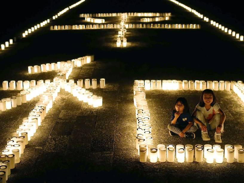 """Garotas sentam ao lado de velas dispostas no formato do símbolo chinês que significa """"paz"""". A celebração comemora os 71 anos desde o fim da Guerra de Okinawa, na China - 23/06/2016"""