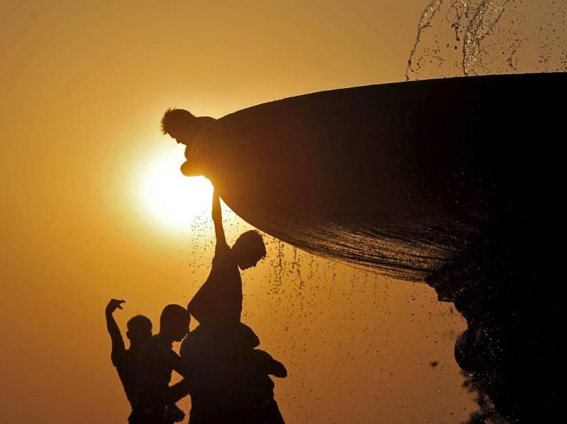 Meninos sobem em uma fonte para se refrescar do forte calor em Nova Délhi, na Índia - 25/04/2016
