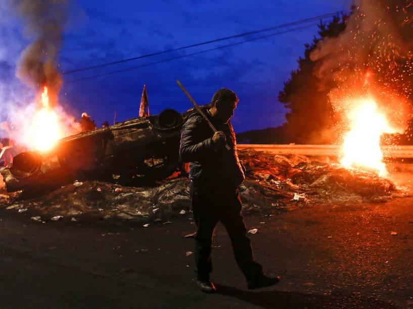 Pescador passa por barricadas que bloqueavam uma estrada, durante protestos pela melhora da economia, na Ilha de Chiloé, no Chile - 05/05/2016