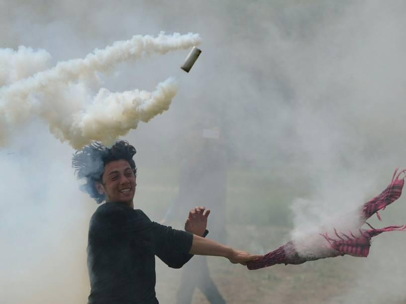 Homem joga de volta para a polícia uma bomba de gás lacrimogêneo durante confronto com imigrantes e refugiados que tentam quebrar a cerca da fronteira com a Macedônia, na cidade grega de Idomeni - 13/04/2016