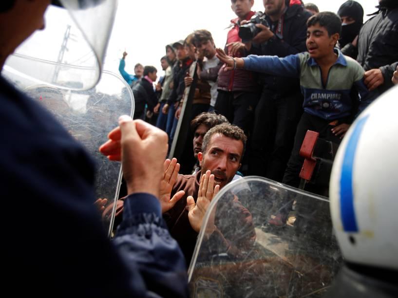 Refugiados sírios lutam contra polícia grega, depois de tentarem derrubar um ônibus da polícia, a fim de entrarem na Macedônia, cujas fronteiras estão fechadas há pelo menos duas semanas - 11/04/2016
