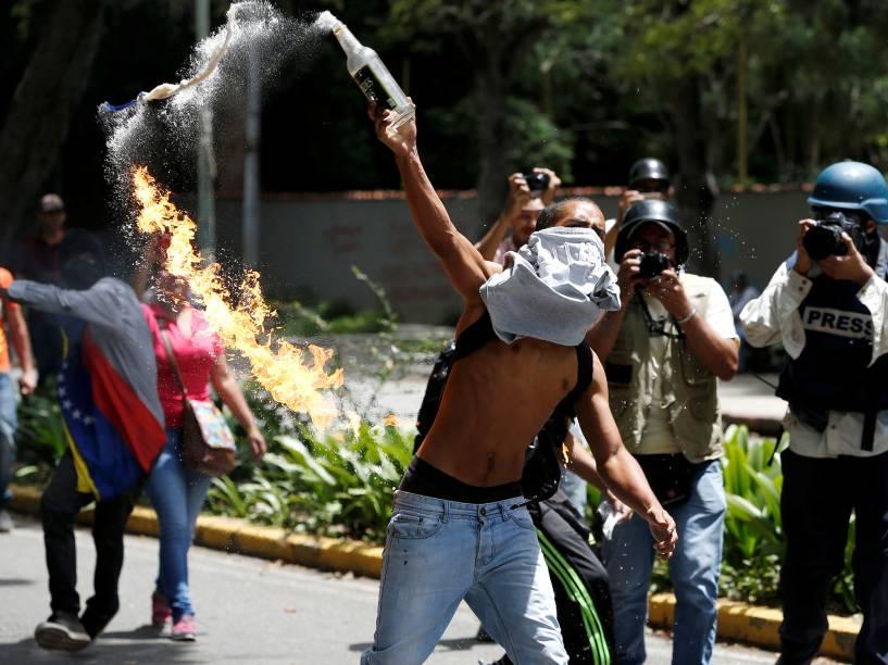 Estudante arremessa coquetel molotov em direção a polícia venezuelana, durante protestos contra o governo, em Caracas, capital da Venezuela - 09/06/2016