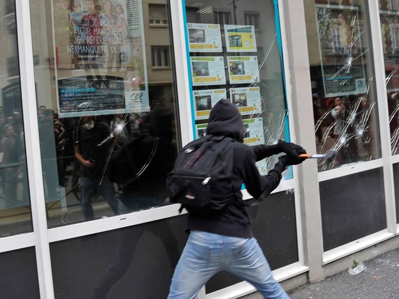 Manifestante mascarado quebra a vidraça de uma agência bancária em Rennes, oeste da França, durante protesto contra as reformas da lei trabalhista proposta pelo governo - 23/06/2016