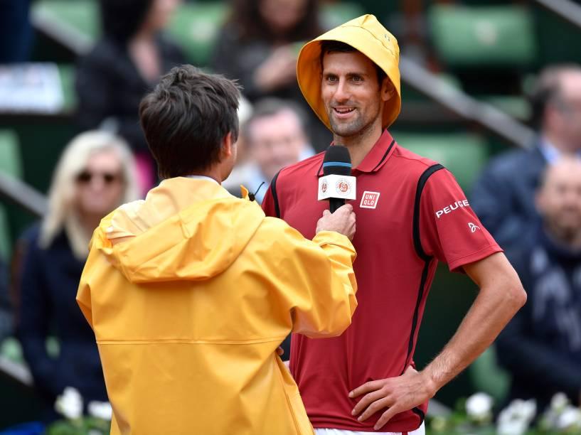 O sérvio Novak Djokovic usa um capuz de capa de chuva enquanto é entrevistado pelo ex-tenista francês Fabrice Santoro após vitória sobre o espanhol Roberto Bautista, em Roland Garros - 01/06/2016