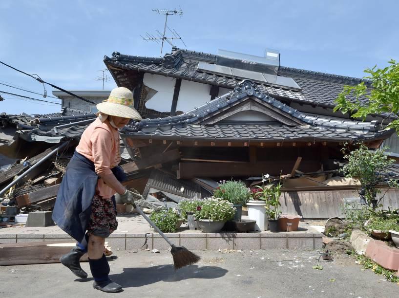 Mulher limpa a frente de sua casa que desabou após terremoto que atingiu a cidade de Mashiki, prefeitura de Kumamoto, no Japão - 15/04/2016