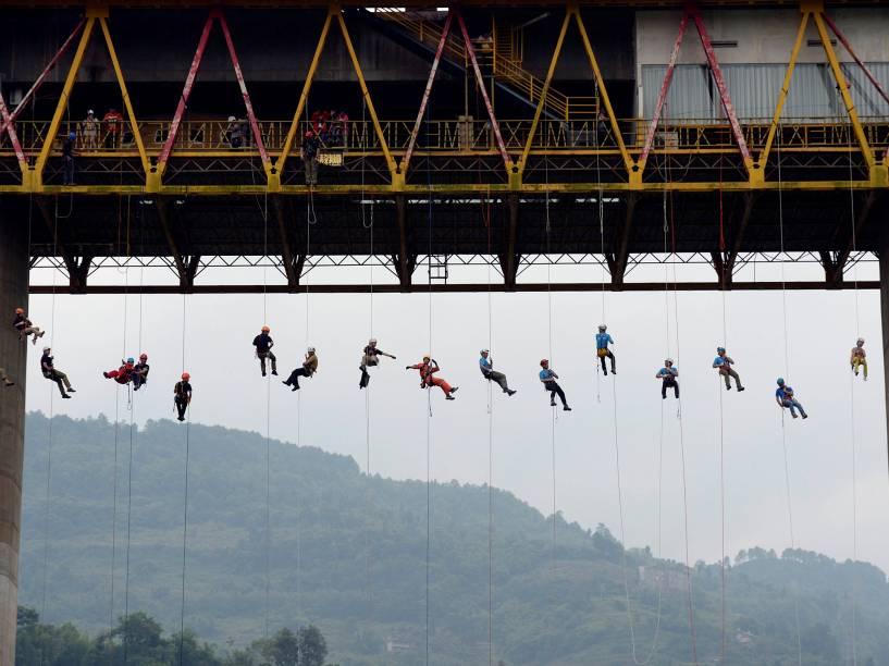 Pessoas escorregam por corda de uma ponte durante um treinamento de resgate na cidade de Chongqing, na China - 23/05/2016