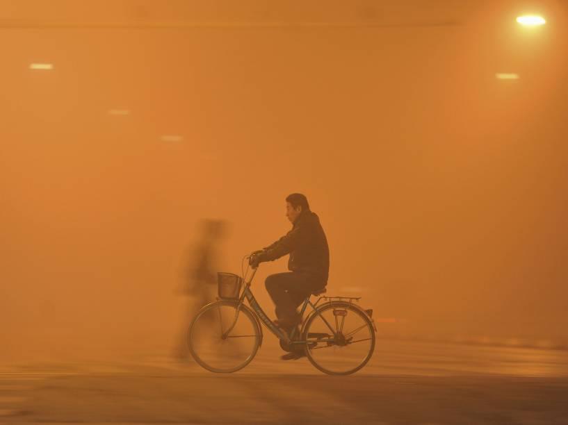 Homem andou de bicicleta sob forte neblina em Fuyang, na China. A névoa causada pela poluição atingiu diversas partes do norte e do leste da China
