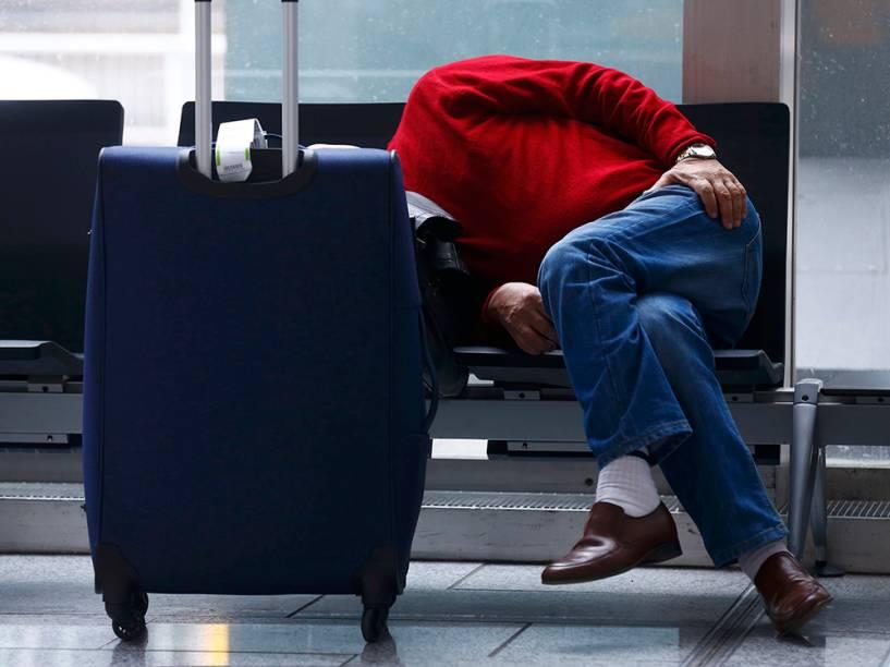 Um passageiro dorme no aeroporto de Frankfurt, na Alemanha, após a companhia aérea Lufthansa cancelar centenas de voos depois que funcionários entrarem em greve