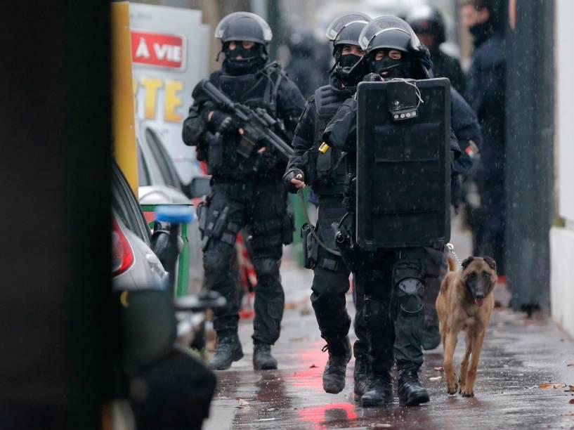 Membros da polícia francesas caminham com um cão farejador na cena de um tiroteio na rua de Montrouge, nos arredores de Paris, no local onde um policial foi morto nesta quinta-feira - 08/01/2015