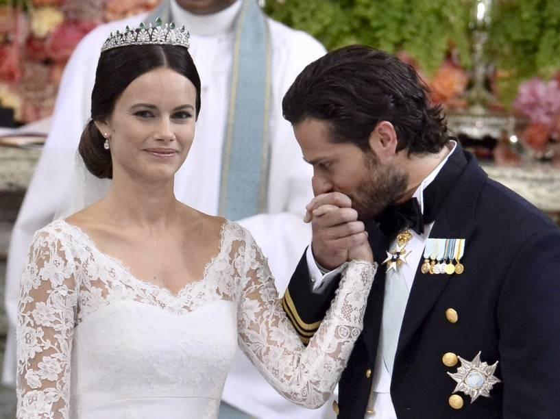 Príncipe sueco Carl Philip beija a mão de Sofia Hellqvist durante a troca de votos e anéis em seu casamento na Capela Real do Palácio de Estocolmo
