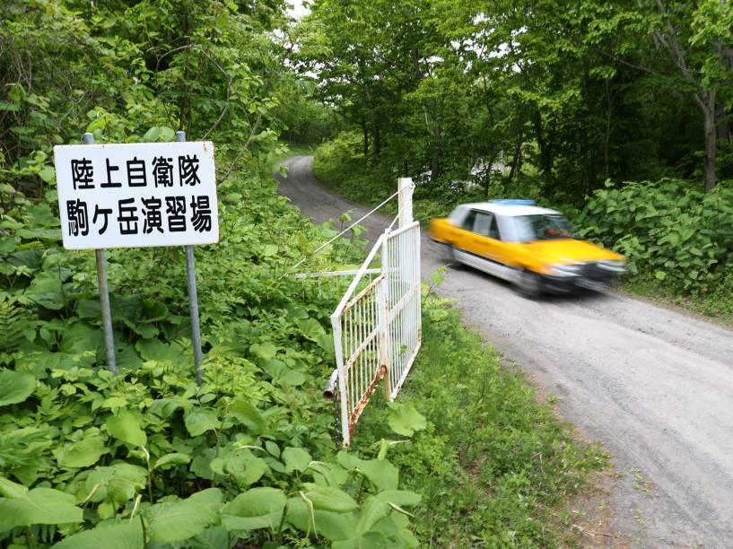 Carro passa na entrada de uma área de exercícios militares na cidade japonesa de Shikabe em Hokkaido local onde o menino de sete anos desaparecido passou quase uma semana abrigado - 03/06/2016