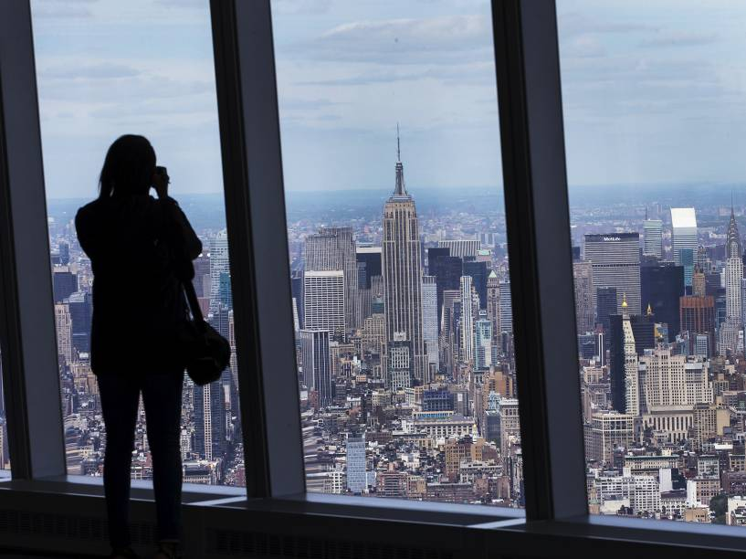 Mulher fotografa o horizonte de Manhattan a partir do deck de observação da torre do One World Trade Center, em Nova York