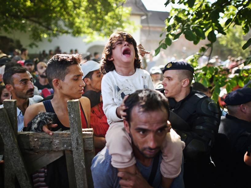 Criança chora nos ombros de seu pai enquanto eles tentam atravessar um bloqueio policial para chegar à estação de Tovarnik na tentativa de embarcar em um trem com destino a Zagreb, na Croácia - 17/09/2015