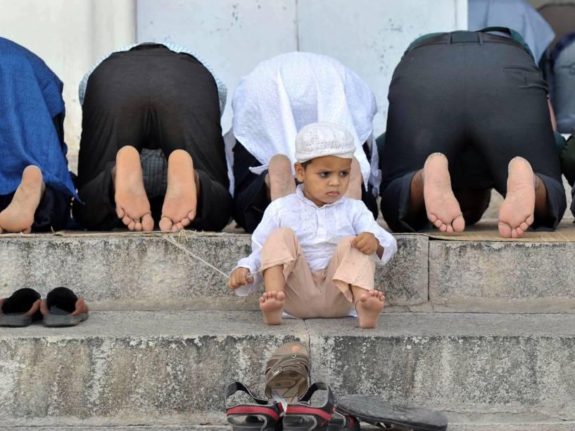 Criança muçulmana sentada em escadaria, enquanto fiéis fazem orações, em Hyderabad, na Índia - 10/06/2016