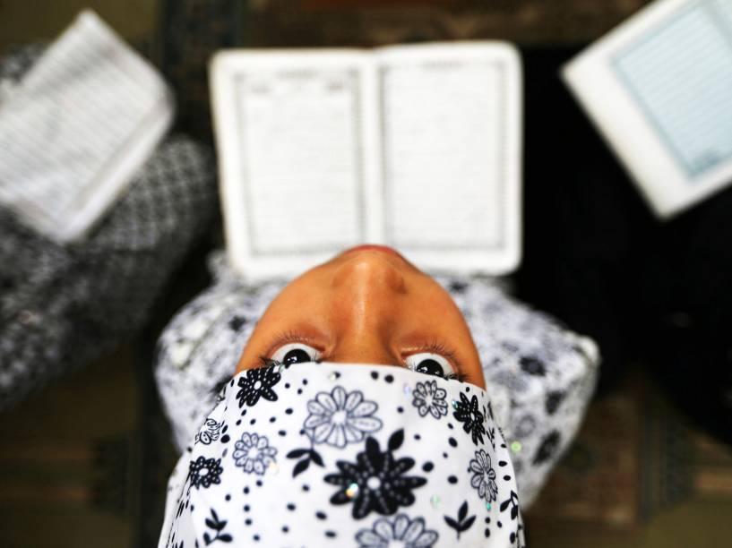 Garota palestina lê o Alcorão, durante o mês de jejum sagrado do Ramadã, em uma mesquita de Rafah, na Faixa de Gaza - 08/06/2016