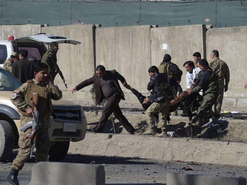 Forças de segurança afegãs carregam uma vítima no local de um atentado com um carro-bomba próximo a uma base da polícia em Cabul - 01/02/2016