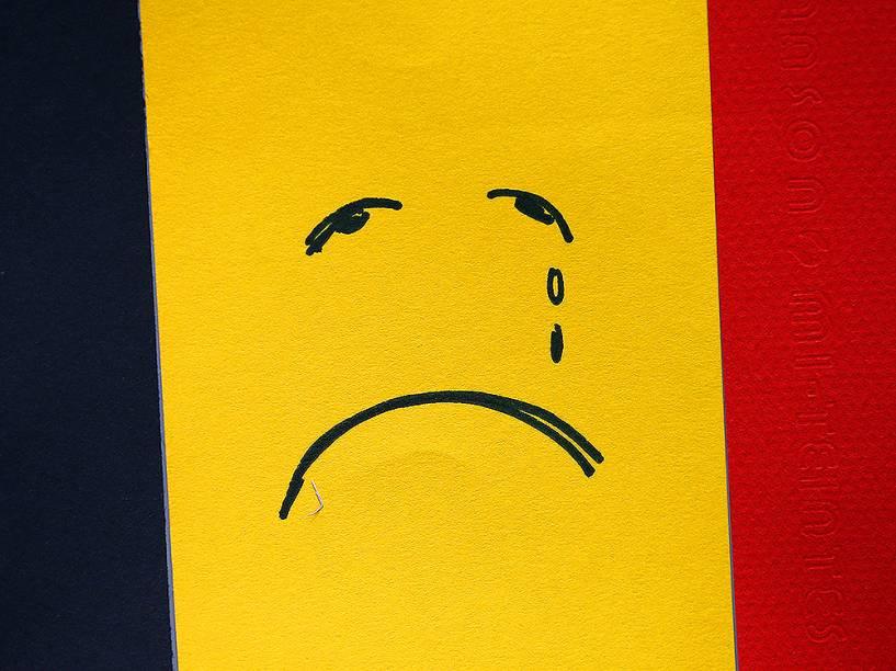 Rosto triste é desenhado em bandeira belga, nesta quarta-feira (23), próximo à estação de metrô Maelbeek, um dos locais que sofreu os atentados em Bruxelas