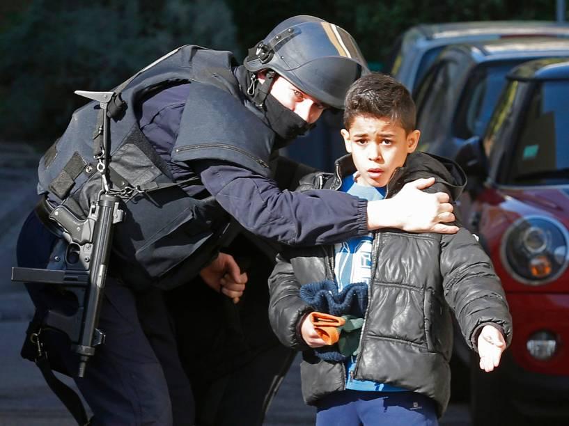 Policial fala com uma criança que estava a caminho de uma escola em Marselha, na França. Homens encapuzados e armados com fuzis dispararam contra a polícia - 09/02/2015