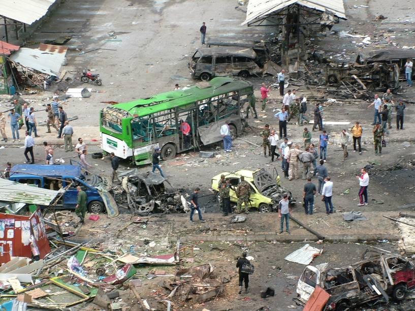 Civis e policiais observam danos causados por explosões terroristas na cidade de Tartous, na Síria - 23/05/2016