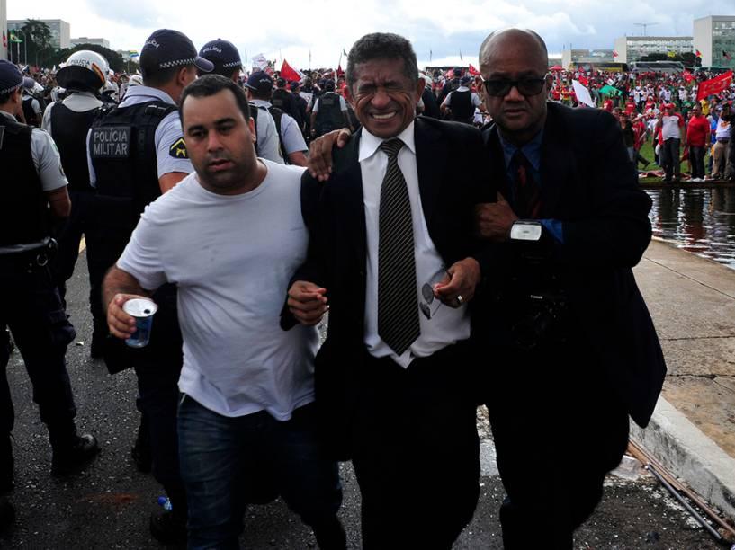O deputado Vicentinho (PT-SP) é retirado de de confusão durante protesto de Centrais Sindicais no gramado do Congresso