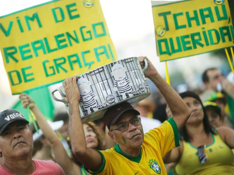 Manifestantes levantam cartaz em protesto a favor do Impeachment, em Copacabana, no Rio de Janeiro, enquanto aguardam pelo início das votações na Câmara dos Deputados - 17/04/2016