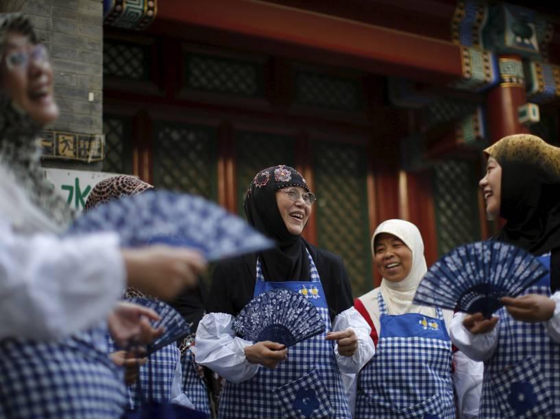 Muçulmanas conversam enquanto preparam comida para o desjejum com outros devotos no primeiro dia do mês sagrado do Ramadan, em Pequim, China