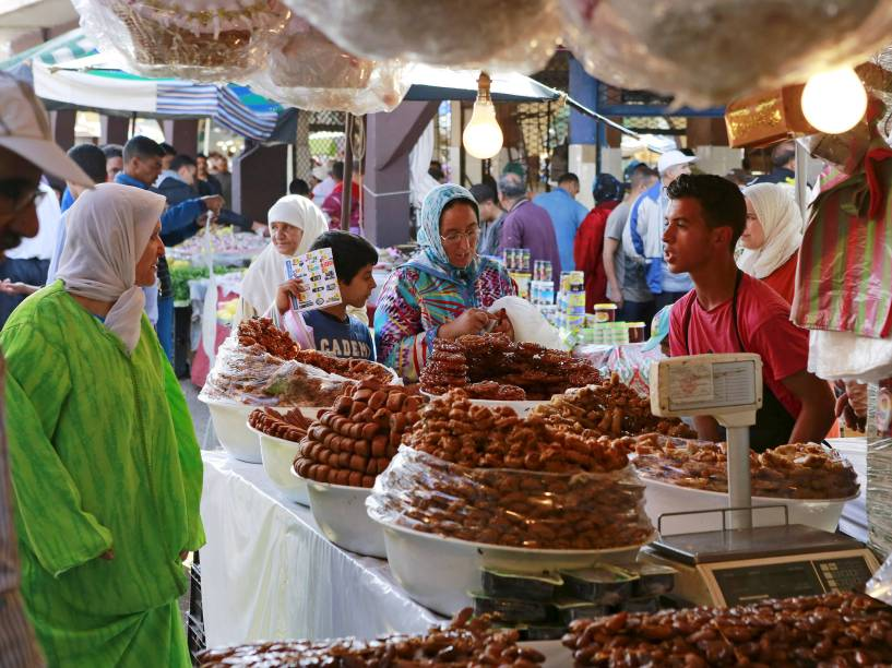 Comerciante vende bolos tradicionais feitos de mell e iguarias para clientes durante o primeiro dia do Ramadã, Oujda, Marrocos