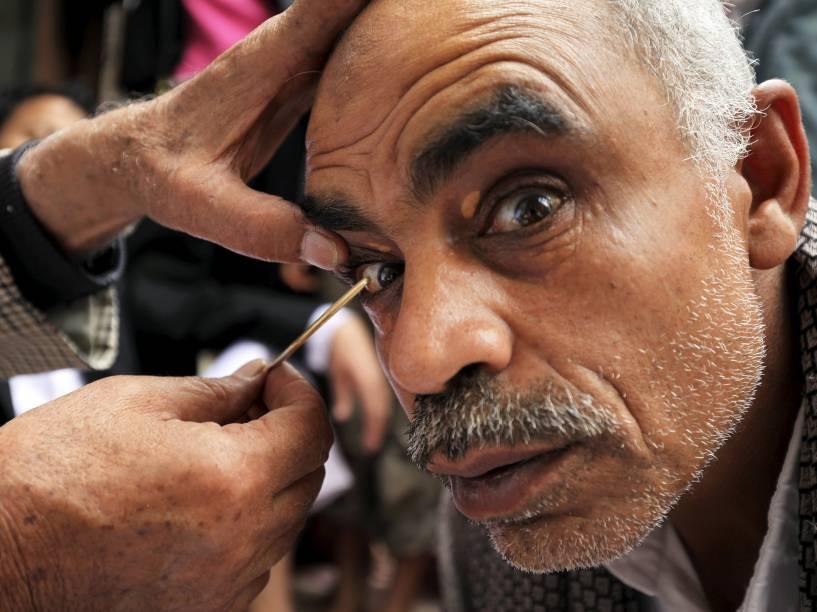 """Homem tem """"kohl"""" aplicado em seus olhos durante o mês sagrado do Ramadã, em Sanaa, Iêmen. O uso do cosmético é uma tradição popular no país"""
